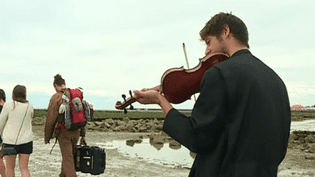 Un des violonistes du groupe Zef rejoint à pied et en musique l'île de Tatihou.  (France 3 Culturebox (capture d'écran))