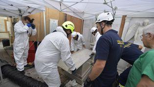 Des enquêteurs et des pompiers ouvrent une tombe dans un cimetière allemand de la Cité du Vatican, le 11 juillet 2019. (VATICAN MEDIA / AFP)