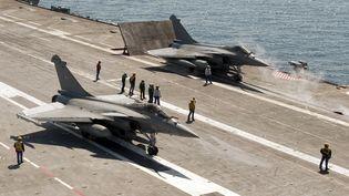 Deux rafales prêts à décoller sur le porte avion Charles de Gaulle, le 25 mars 2011. (AFP PHOTO / MARINE NATIONALE / CYRIL DAVESNE)