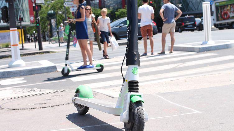 Une trottinette électrique en libre service (de la marque Lime) sur un trottoir, juste devant un passage piéton et une piste cyclable,le 6 juillet 2019 à Paris. (AURÉLIEN ACCART / RADIO FRANCE)