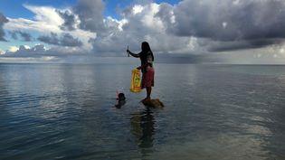 Des habitants de l'achipel de Kiribati, le 13 juin 2013.Ces îles sont parmi les territoires les plus menacés par les réchauffement climatique. (DAVID GRAY / REUTERS)