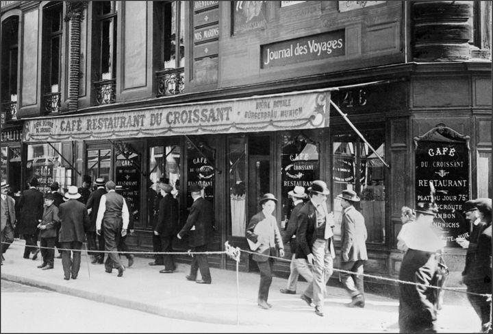 Des passants circulent devant le café du Croissant, à Paris, le 1er août 1914, au lendemain de l'assassinat de Jean Jaurès dans cet établissement. (AFP)