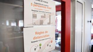 Les règles de distanciation sociale affichées à l'entrée d'une entreprise. (REMI DUGNE / MAXPPP)