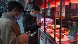 Des passants portent des masques à Pékin, le 25 février 2020. (GREG BAKER / AFP)