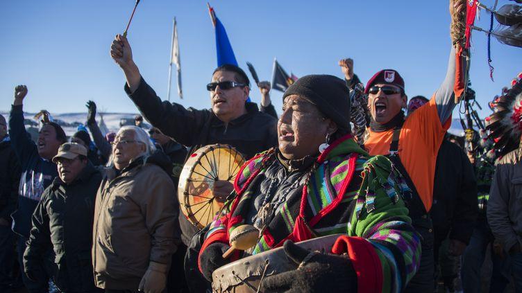 Des manifestants célèbrent le rejet du projet controversé d'oléoduc qui devait traverser les territoires sioux à Cannon Ball, dans le Dakota du Nord (Etats-Unis), le 4 décembre 2016. (JIM WATSON / AFP)