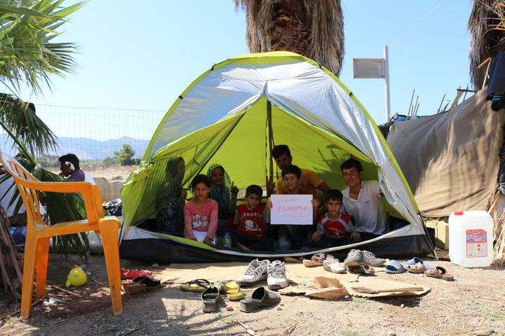 Une famille de migrants afghans sous une tente dans la cour de l'hôtel Captain Elias, le 19 août 2015 à Kos (Grèce). (BENOIT ZAGDOUN / FRANCETV INFO)