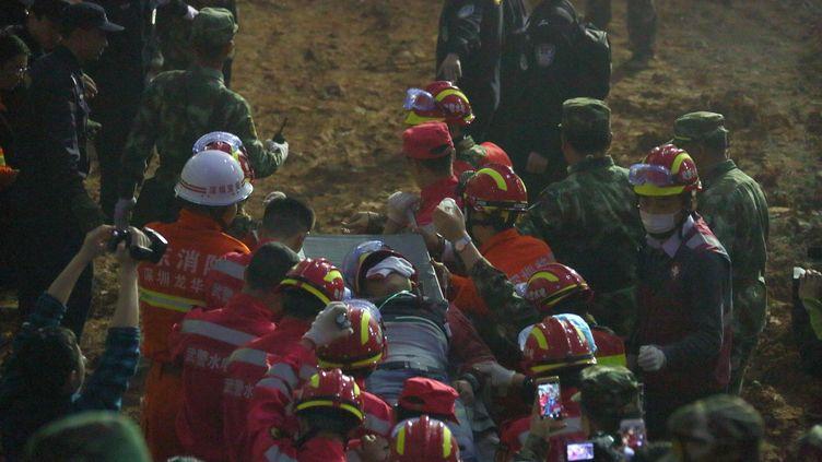Un survivant est extrait des décombres du glissement de terrain à Shenzhen (Chine), le 23 décembre 2015. (YIN GANG / XINHUA / AFP)