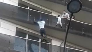 Mamoudou Gassamasauvant un enfant suspendu dans le vide, dans le 18e arrondissement de Paris, samedi 26 mai 2018. (FACEBOOK)