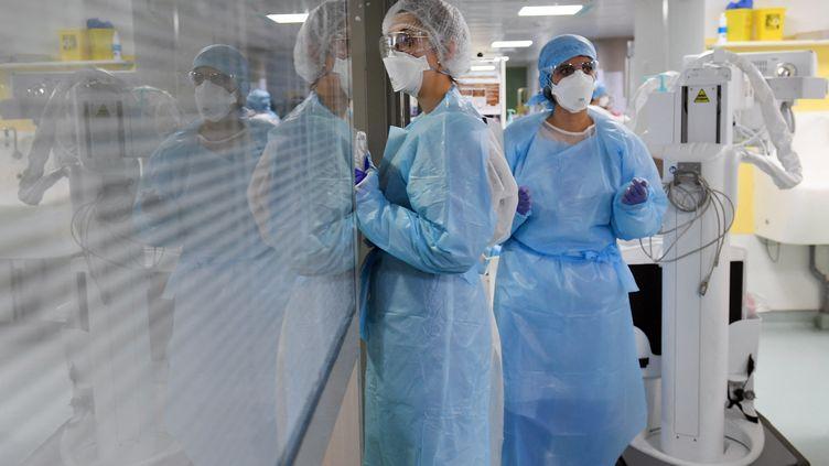 Deux infirmières attendent dans le couloir d'un service de détresse respiratoire où sont traités les malades atteints du Covid-19 à l'Hôpital Marseille Nord le 2 février 2021. (NICOLAS TUCAT / AFP)