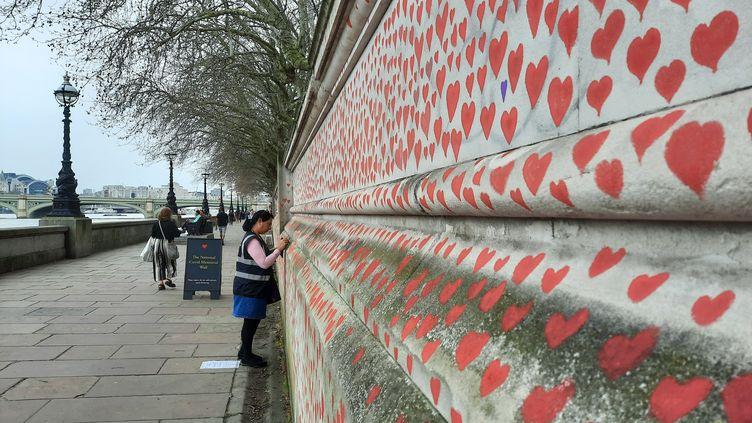 Des cœurs sont dessinées par des bénévoles à Londres au bord de la Tamise en hommage aux victimes de l'épidémie de Covid-19. (RICHARD PLACE / RADIO FRANCE)