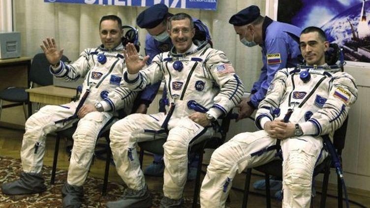 L'astronaute américainDan Burbank (au centre), entouré des deux cosmonautes russesAnton Shkaplerov (gauche) et Anatoly Ivanishin (droite), le 14 novembre 2011 à Baïkonour (Russie). (MIKHAIL METZEL / POOL / AFP)