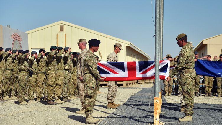 Des soldats britanniques baissent leur drapeau sur la base militaire de Camp Bastion, dans la région du Helmand, en Afghanistan, le 26 octobre 2014. (SERGEANT OBI IGBO / CROWN COPYRIGHT 2014 / AFP)