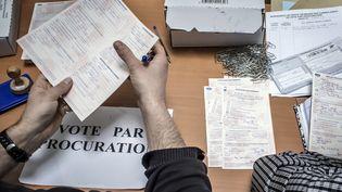 Des employés vérifient les demandes de procuration qu'ils reçoivent, le 11 avril 2012, dans un commissariat de Lyon (Rhône). (JEAN-PHILIPPE KSIAZEK / AFP)