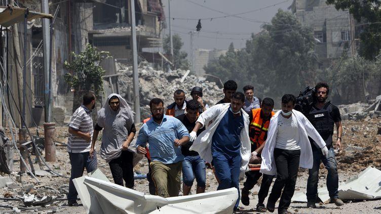 Les secours évacuent un corps à Chajaya, en banlieue de Gaza, le 20 juillet 2014. (MAHMUD HAMS / AFP)