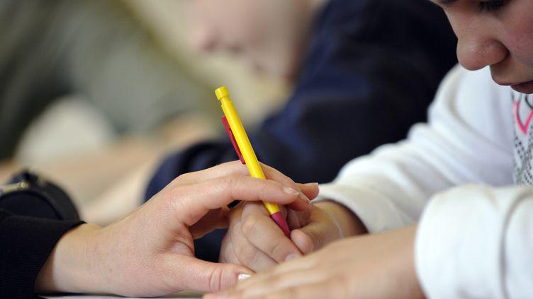 Un enfant autiste travaille avec une éducatrice, le 24 avril 2008, à Paris, à l'institut médico-éducatif Les Petites Victoires. (FRANCK FIFE / AFP)