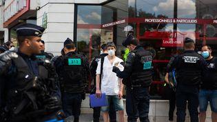 Des policiers contrôlent l'identité de manifestants réclamant plus de moyens pour les soignants, le 21 mai 2020, à Paris. (RAPHAEL KESSLER / HANS LUCAS / AFP)