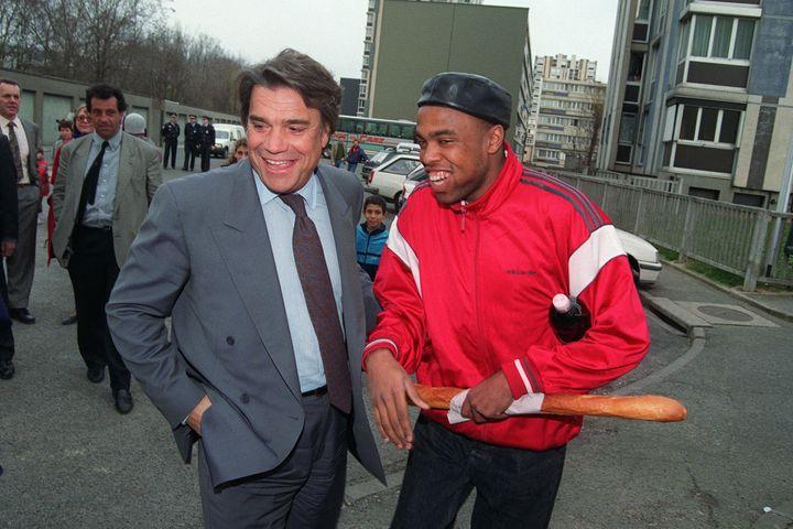 Ministre de la Ville, il plaisante le 10 mars 1993 avec un jeune habitant d'une cité d'Athis-Mons (Essonne). (GEORGES BENDRIHEM / AFP)