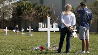 Des Américains rendent hommage aux victimes de la fusillade au lycée Stoneman Douglas de Parkland (Floride), le 16 février 2018. (RHONA WISE / AFP)