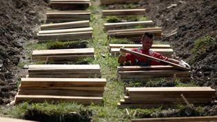 Un employé prépare des tombes au futur mémorial des victimes du massacre de Srebrenica à Potocari (Bosnie-Herzégovine), le 7 juillet 2014. (DADO RUVIC / REUTERS)