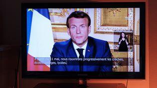 Une télévision diffuse l'allocution d'Emmanuel Macron, le 13 avril 2020. (NICOLAS PORTNOI / HANS LUCAS / AFP)