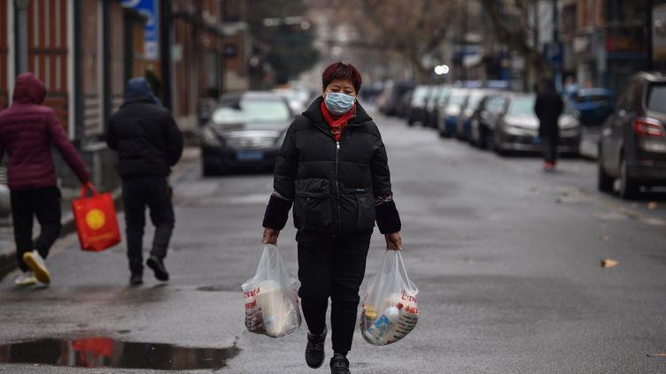 Une femme revient d'un marché àWuhan(Chine), le 26 janvier 2020. (HECTOR RETAMAL / AFP)
