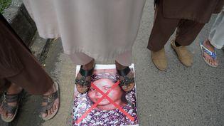 Des militants d'un parti islamiste marchent sur une photo d'Asia Bibi, dans une manifestation contre sa libération, à Islamabad (Pakistan), le 2 novembre 2018. (AAMIR QURESHI / AFP)