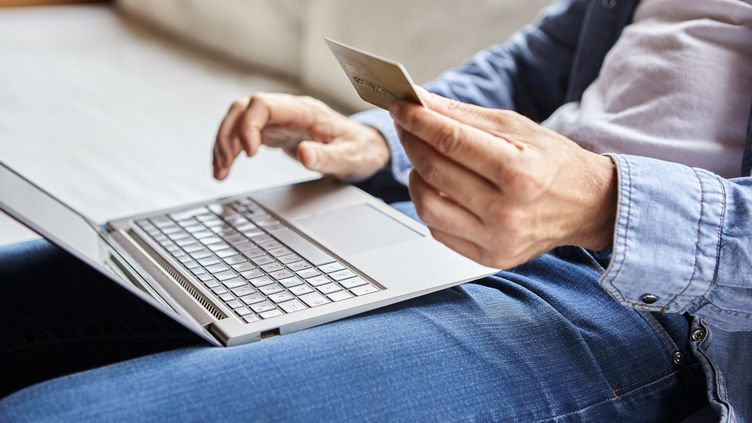 Un homme procède à un achat en ligne. Photo d'illustration. (DINOCO GRECO / MAXPPP)