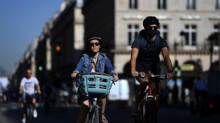Des cyclistes circulent dans Paris, le 30 juillet 2020. (CHRISTOPHE ARCHAMBAULT / AFP)