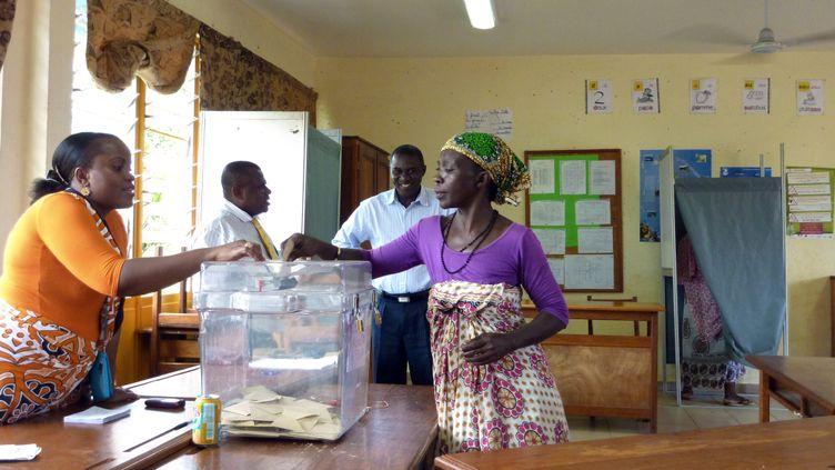 Une femme dépose son bulletin dans un bureau de vote de Koungou (Mayotte), le 20 mars 2011. (SOPHIE LAUTIER / AFP)