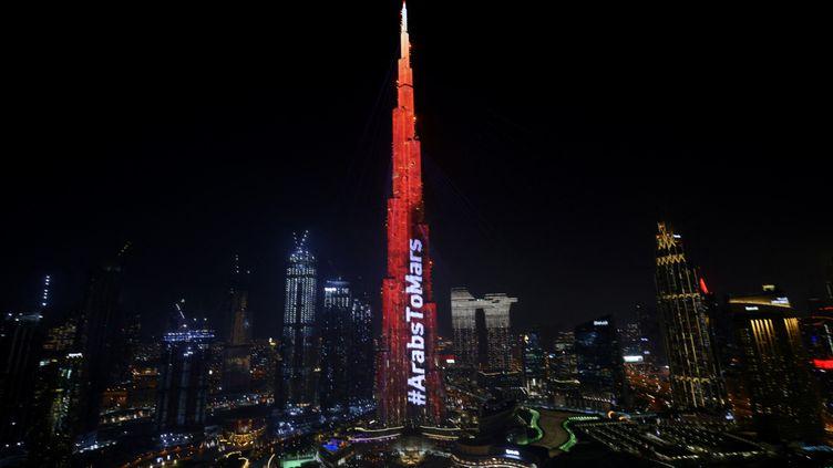 """Le Burj Khalifa de Dubaï est éclairé en rouge le 9 février 2021 alors que la sonde des Emirats Arabes Unis """"Amal"""" - en arabe pour """"Hope"""" - effectue une manœuvre délicate pour entrer sur l'orbite de la planète rouge. (GIUSEPPE CACACE / AFP)"""
