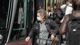 Une femme porte un masque antipollution, le 14 mars 2014, à Grenoble (Isère), lors d'un pic de pollution aux particules fines. (JEAN-PIERRE CLATOT / AFP)