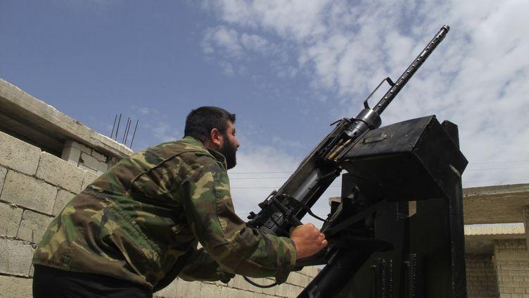 Un rebelle syrien pointe une mitrailleuse vers le ciel, à Idlib (Syrie), le 18 mai 2013. (ABDALGHNE KAROOF / REUTERS)