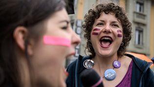 Deux femmes dans les rues de Lausanne, en Suisse, le 14 juin 2019, manifestent pour réclamerdavantage d'égalité salariale. (FABRICE COFFRINI / AFP)