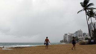 Un couple sur une plage de Porto-Rico, sur la trajectoire de l'ouragan Irma, mardi 5 septembre 2017. (RICARDO ARDUENGO / AFP)
