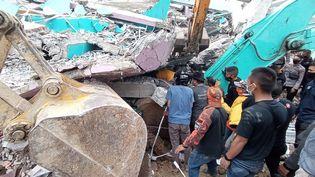 Des secours s'affairent autour d'un bâtiment qui s'est effondré, après un séisme survenu vendredi 15 janvier 2021 à Mamuju (Indonésie). (MAWARDI / AFP)
