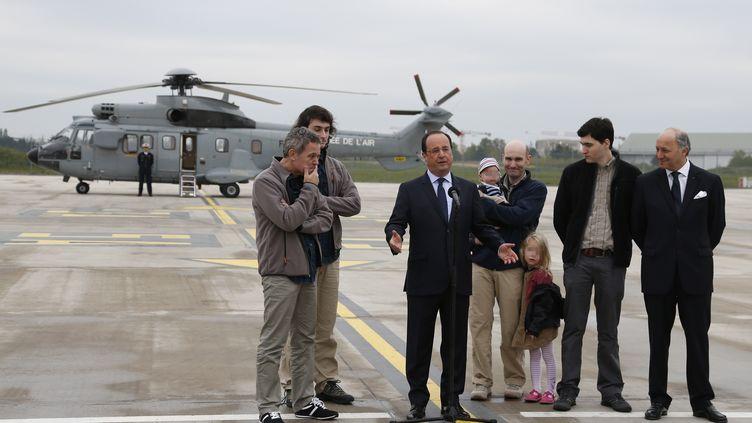François Hollande accueille, sur le tarmac de l'aéroport de Villacoublay, les journalistes ex-otages en Syrie : Didier François, Edouard Elias, Nicolas Hénin et Pierre Torrès. (THOMAS SAMSON / AFP)