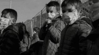 Des élèves, masques sur le visage, sont figés dans leur cour d'école. Nous sommes à quelques kilomètres du Mont-Blanc et c'est le moyen choisi par leurs parents pour alerter sur les conséquences de la pollution. (France 2)