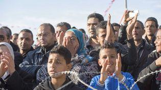 Des Tunisiens applaudissent les forces de sécurité qui évacuent les touristes du musée du Bardo, à Tunis, mercredi 18 mars 2015. ( ANADOLU AGENCY / AFP)