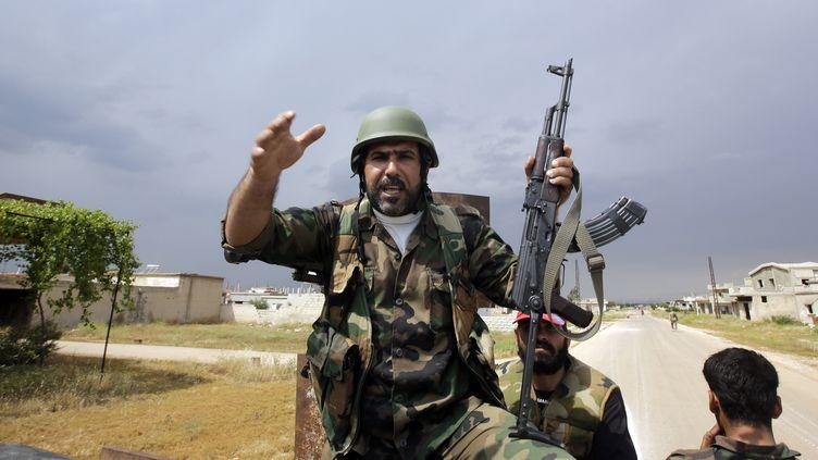 Des militaires syriens, à sept kilomètres de la ville rebelle de Qousseir, le 13 mai 2013. (JOSEPH EID / AFP)