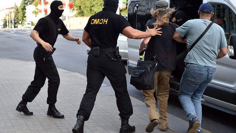 Les policiers anti-émeutes arrêtent un homme lors d'un rassemblement de l'opposition à la veille de l'élection présidentielle, le 8 août 2020, à Minsk, en Biélorussie. (SERGEI GAPON / AFP)