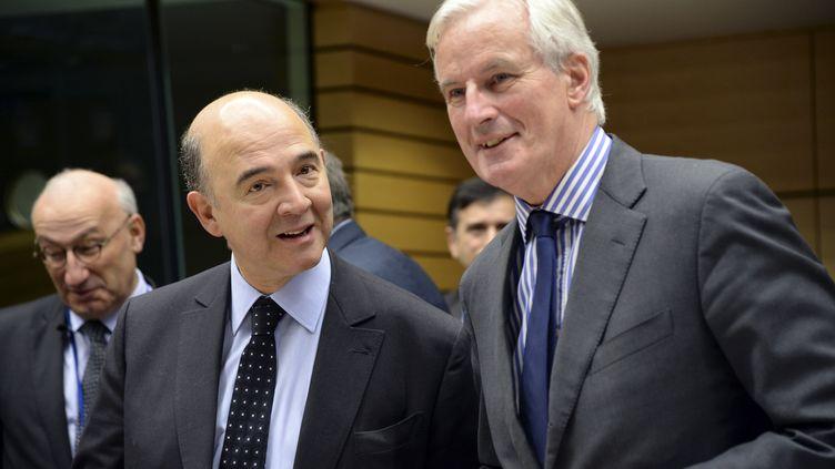 A Bruxelles, le 18 décembre 2013, Pierre Moscovici (ministre de l'Economie) et Michel Barnier (commissaire européen chargé des Services). (THIERRY CHARLIER / AFP)