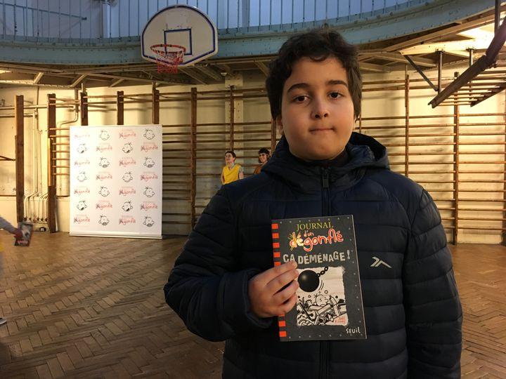 """Younes, 11 ans,élève du collège Georges Rouault (Paris 19e) pose avec Le Jounal d'un dégonflé - Ca déménage !"""" (Seuil Jeunesse), le 10 décembre 2019 (Laurence Houot / franceinfo Culture)"""