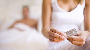 Une femme prend un pilule contraceptive. (IAN HOOTON / I2H / AFP)