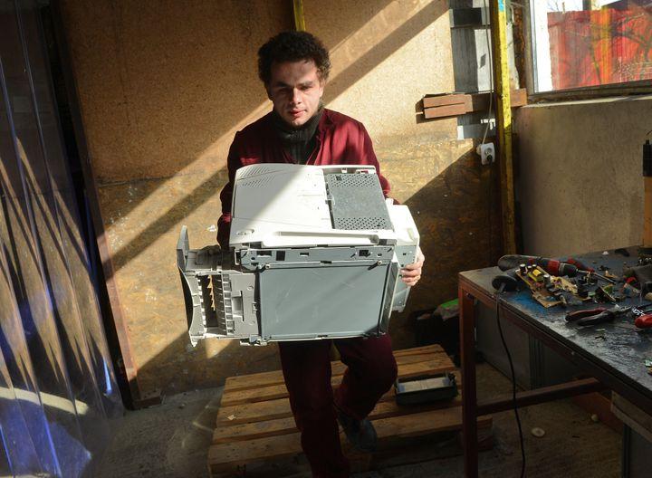 Un Roumain manipule une imprimante défectueuse à l'association Ateliers sans frontières, un centre de recyclage près de Bucarest, la capitale roumaine, le 1er février 2013. (DANIEL MIHAILESCU / AFP)