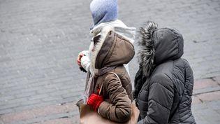 Despersonnes marchent à Lille (Nord), le 26 février 2018, alors qu'une vague de froid en provenance de Sibérie s'installe enFrance.  (PHILIPPE HUGUEN / AFP)