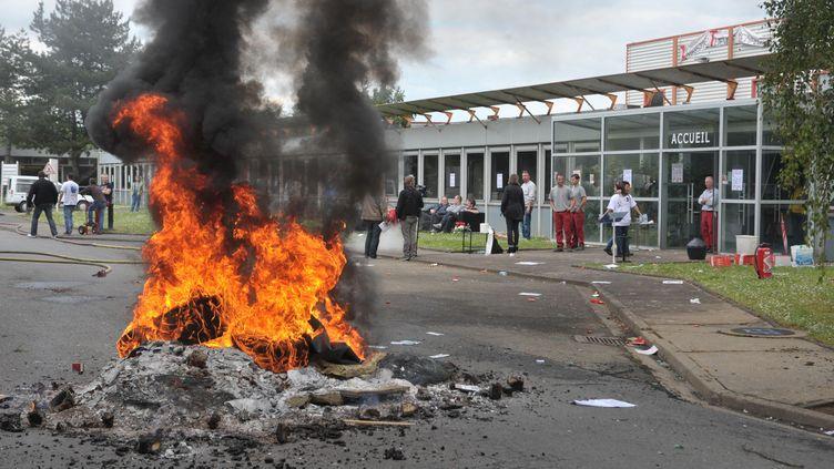 Les salariés grévistes de l'usine Seita de Carquefou (Loire-Atlantique) brûlent des pneus, le 28 mai 2014, pour protester contre la fermeture du site. (MAXPPP)