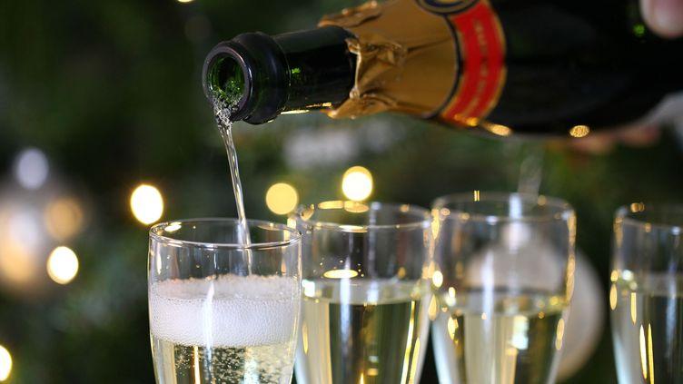 A une grosse soirée de réveillon, exclueen raison de l'épidémie, certains préfèrent du champagne et un bon petit plat en famille devant la télé. (MAXPPP)