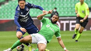 L'attaquant bordelais Hwang Ui-Jo défendu par le Stéphanois Harold Moukoudi le 11 avril 2021 en Ligue 1.  (PHILIPPE DESMAZES / AFP)