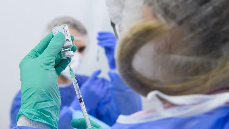 Un employé du centre de vaccination de Dresde (Allemagne) se prépare à administrer le sérum d'AstraZeneca, le 20 mars 2021. (ROBERT MICHAEL / DPA-ZENTRALBILD / AFP)
