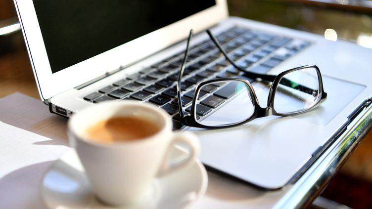 Une paire de lunettes et un ordinateur portable pour travailler chez soi, le 15 mars 2020. (BARBARA GINDL / APA)
